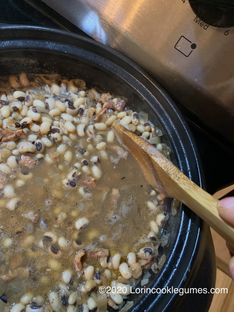 As the beans start to soften, mash some of them against the side of the pot to thicken the broth.